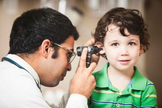 A doctor examining a child's ear representing the family medicine practice at Heart of Ohio Family Health in Columbus, OH